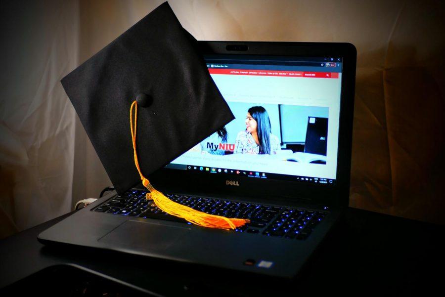 graduation cap sits atop a laptop