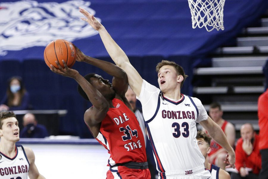 Dixie State guard Emad Elniel (34) shoots and is fouled by Gonzaga forward Ben Gregg (33) during the second half of an NCAA college basketball game in Spokane, Wash., Tuesday, Dec. 29, 2020. Gonzaga won 112-67.