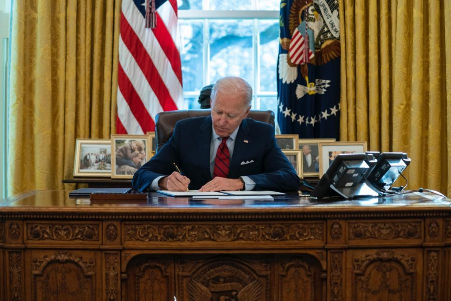 President Joseph Biden sits and signs executive orders Thursday in the Oval Office in Washington D.C.