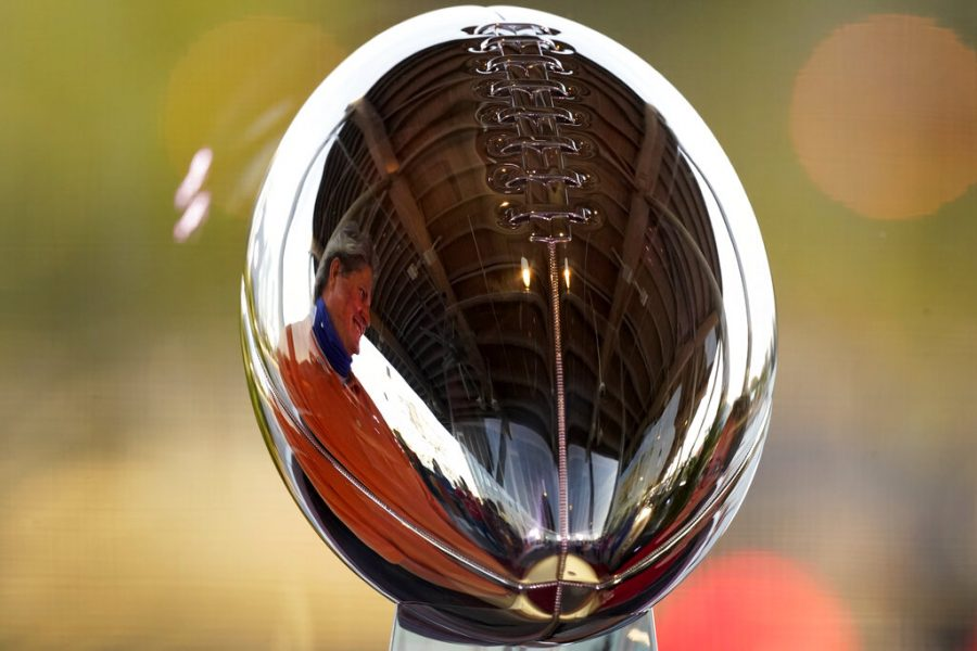 A man looks at the Lombardi Trophy at the NFL Experience Thursday, Feb. 4, 2021, in Tampa, Fla. The city is hosting Sundays Super Bowl football game between the Tampa Bay Buccaneers and the Kansas City Chiefs. (AP Photo/Charlie Riedel)