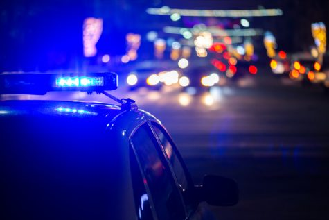 A police car has its lights  on at a busy road at night.