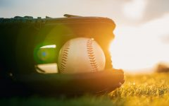 Baseball in glove in the lawn at sunset in the evening day with sun ray and lens flare light.
