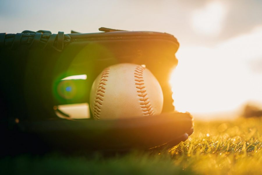 Baseball+in+glove+in+the+lawn+at+sunset+in+the+evening+day+with+sun+ray+and+lens+flare+light.