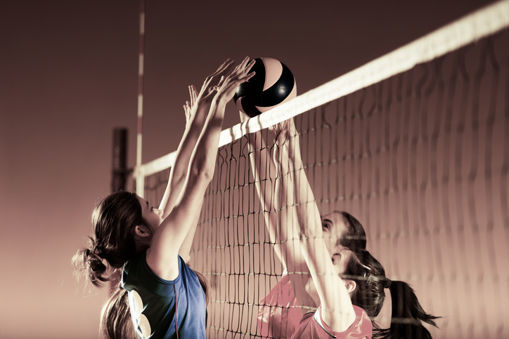 Female volleyball players on the net.