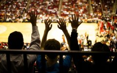 Unrecognizable people raise hands in excitement during a basketball sports game inside a large basketball sports stadium. Basketball court seen below. Silhouette. Cheering fans.