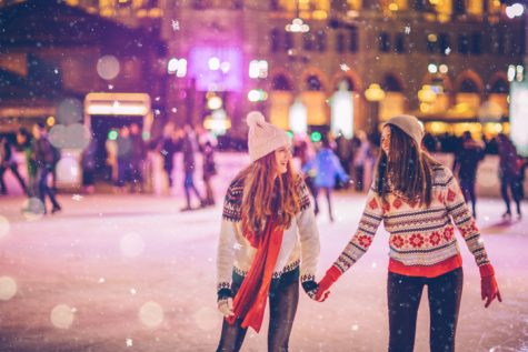 Couple having so much fun while ice skating at night. Wearing warm clothing. City is decorated with christmas lights.