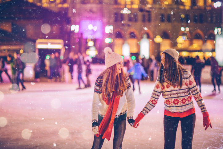 Couple+having+so+much+fun+while+ice+skating+at+night.+Wearing+warm+clothing.+City+is+decorated+with+christmas+lights.