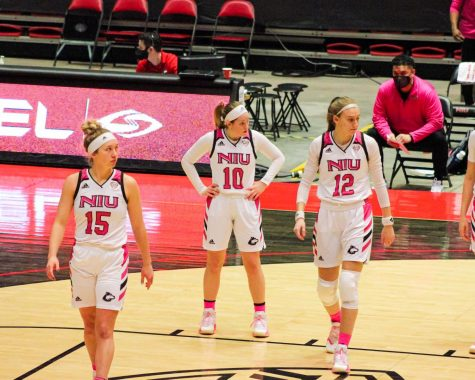 NIU sophomore guards Grace Hunter (left), Chelby Koker (center) and senior forward Riley Blackwell (right) wait for play to resume Feb. 20, during NIU