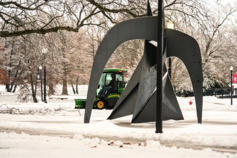 Snow being cleared from sidewalks near the Central Quad sculpture Dec. 30.