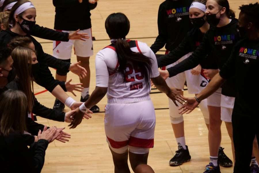 NIU sophomore forward A'Jah Davis (center) high-fives her teammates Feb. 3, during the announcement of the starting lineups at the NIU Convocation Center in DeKalb.