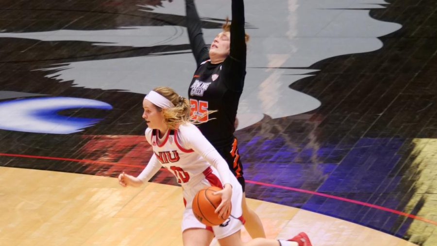 NIU sophomore guard Chelby Koker (front) drives past a Bowling Green State University defender Feb. 3, during NIU's 79-78 win over the Falcons at the NIU Convocation Center in DeKalb.