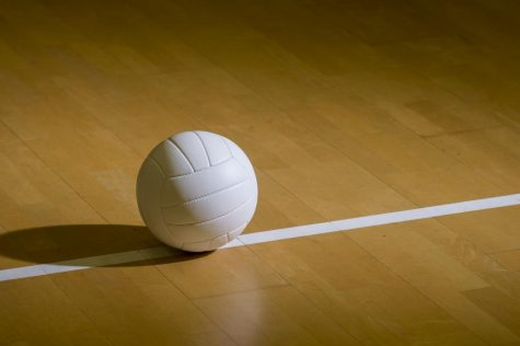 Volleyball on a wood court floor.