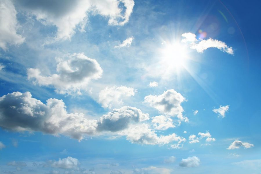Sunshine streams through a cloud covered sky.