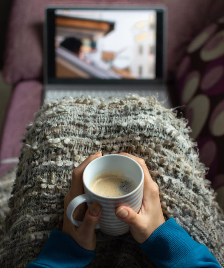 A woman in a blanket sits  with a coffee cup watching a video on her laptop.