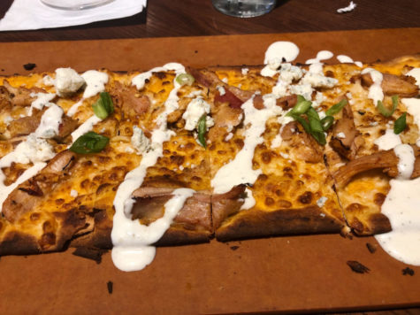 Square pizza drizzled in ranch sits in cardboard pizza box.