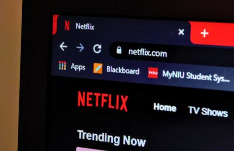 The Netflix home page shows a list of trending shows on a laptop screen.