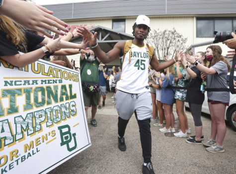 Baylor junior guard Davion Mitchell slaps hands with fans after arriving home as NCAA college basketball champions April 6, 2021, in Waco, Texas.