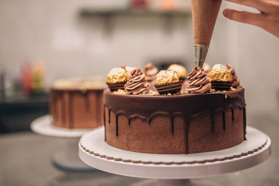 Confectioner decorating chocolate cake, close-up.