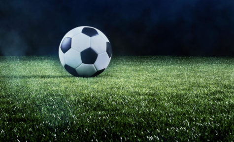 Football or soccer background with a row of spotlights illuminating a ball on the green turf in a stadium in a sports championship or World Cup event in a panorama banner