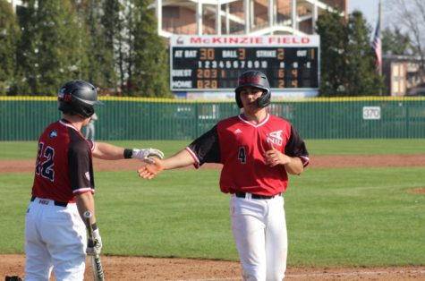 Redshirt senior catcher Jake Dunham (right) recieves a high-five after scoring a run in the second half of an April 3 doubleheader against the Central Michigan Chippewas at Ralph McKinzie Field.
