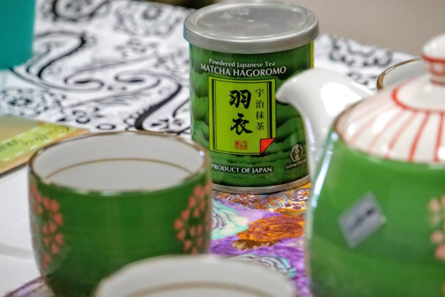 A can of powdered matcha hagoromo sits on the table with other tea trinkets.