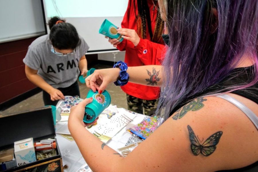 Chinese Club president Angel Alba puts a sticker on her personalized tea cup.