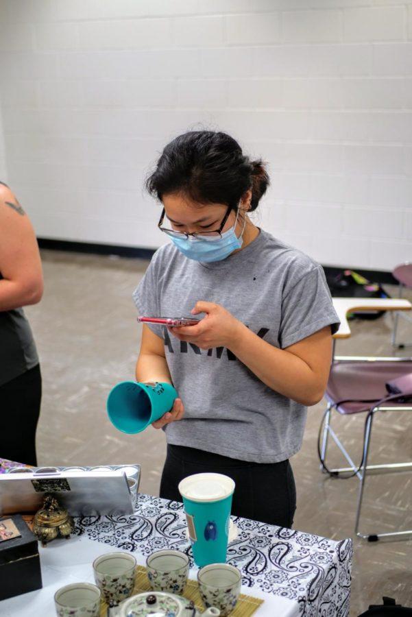 Junior, education major Hannah Schaumberg takes a photo of her tea cup design.