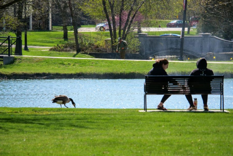 Two NIU students sit on a bench Thursday at the East Lagoon.