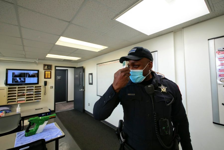 NIU police officer Larry Williams checks his temperature Thursday at the NIU Police Department.