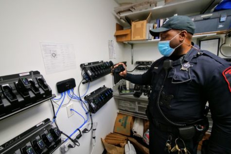 NIU police officer Larry Williams checks his body camera Thursday before putting it on his uniform. All NIU officers are assigned their own body camera.