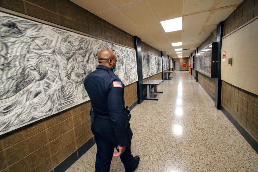 Officer Larry Williams walks down a hallway Thursday in the art building.