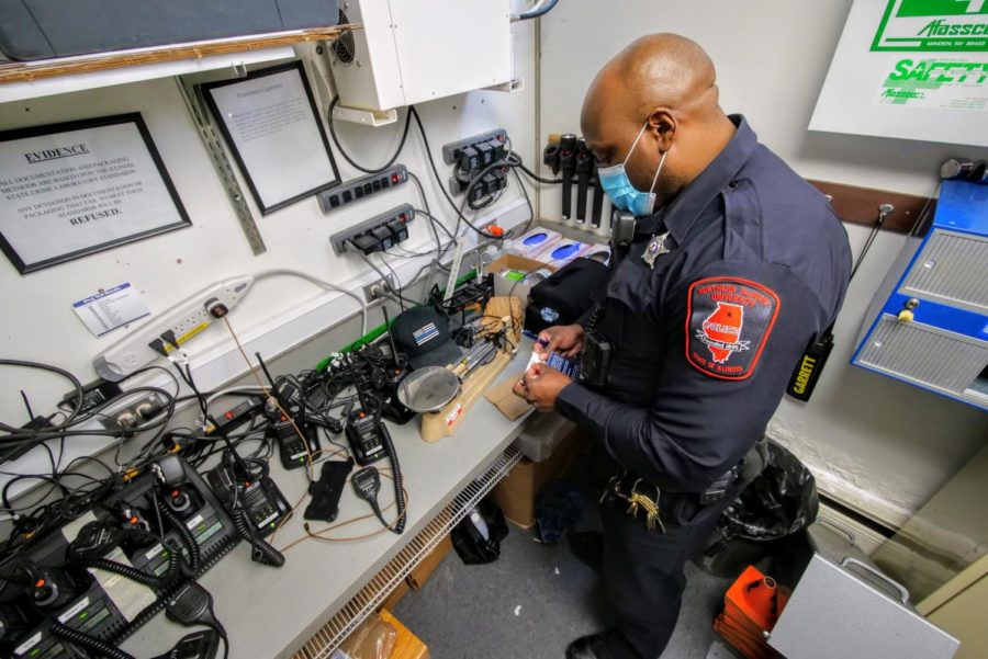 Officer Larry Williams demonstrates how to log evidence in a bag Thursday at the NIU police department.