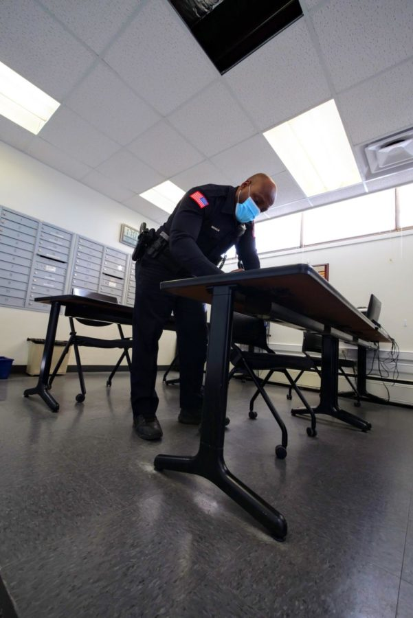 Officer Larry Williams logs his building check of the art building Thursday at the NIU police department.
