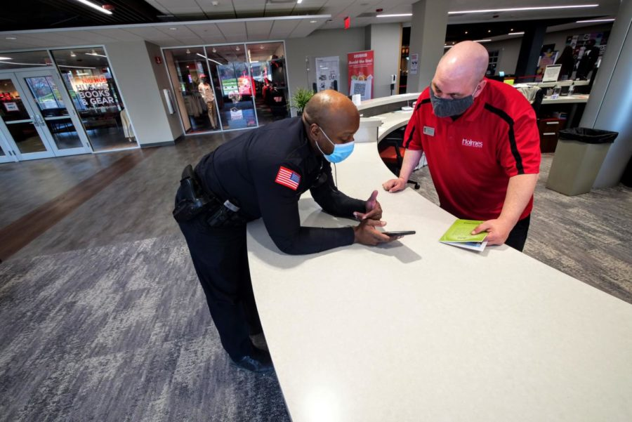 Officer Larry Williams asks for assistance from Main Desk Attendant Thomas Koron Thursday at the front desk of the Holmes Student Center.