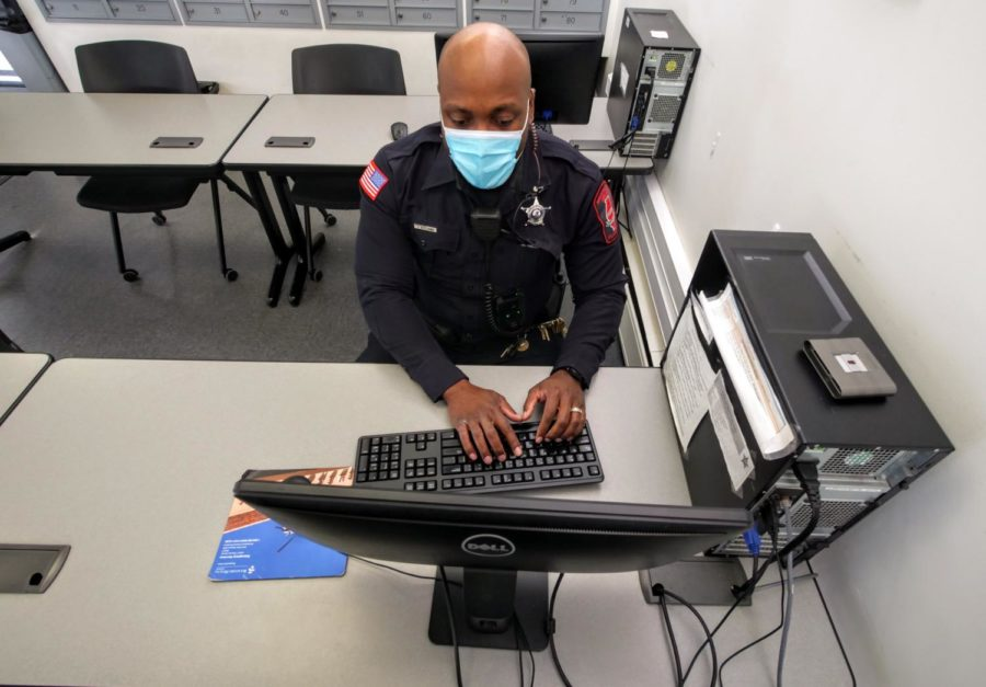 Officer Larry Williams reviews body camera footage on a computer Thursday at the NIU police department.