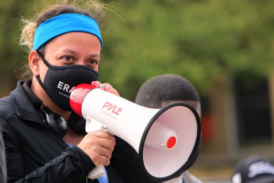 DeKalb community member Jocelyn Santana speaks to a group of BLM supporters Friday with a megaphone.