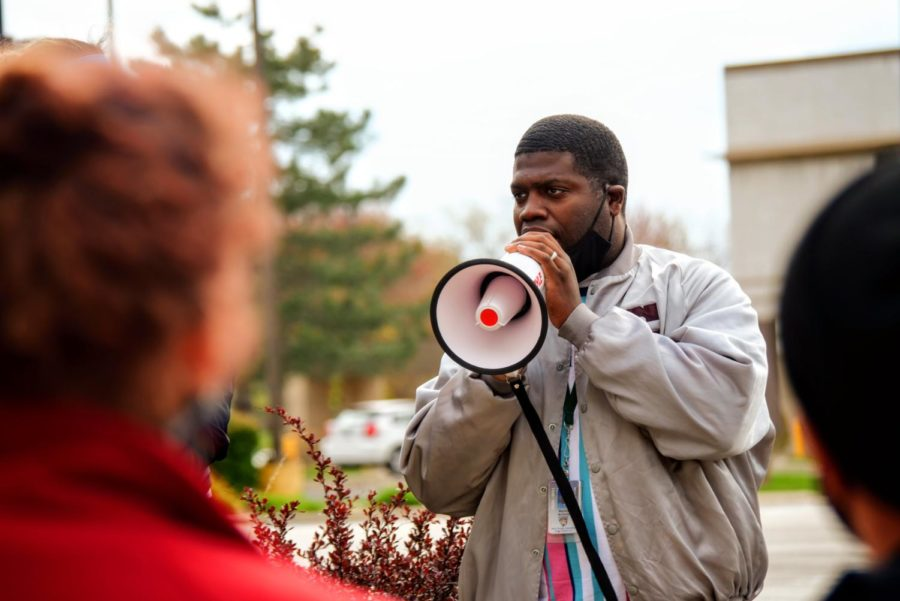 Maurice McDavid speaks to the crowd Friday with a megaphone. The vigil was held in memory of Daunte Wright, Adam Toledo, George Floyd, and all the people who lost their lives to state-sanctioned violence.