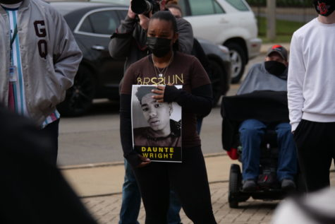 Jessica Webb, of DeKalb, holds a Daunte Wright sign on Friday during the vigil at Memorial Park.