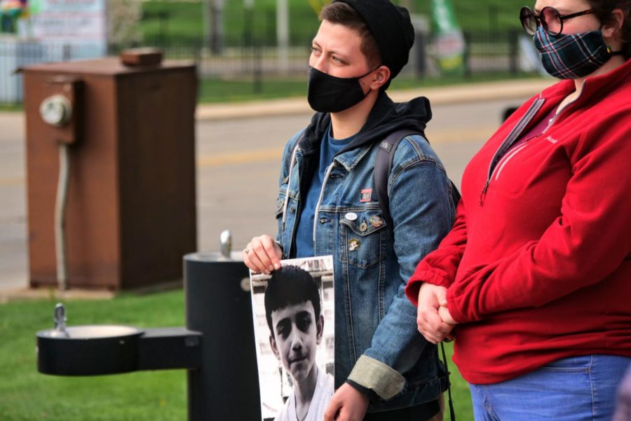 Assistant director of social justice education, Jane Pappas holds a poster of Adam Toledo Friday at a vigil in Memorial Park.
