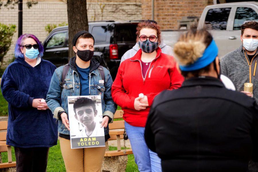 Jane Pappas holds a sign of Adam Toledo Friday at Memorial Park in DeKalb while listening to Jocelyn Santana speak.
