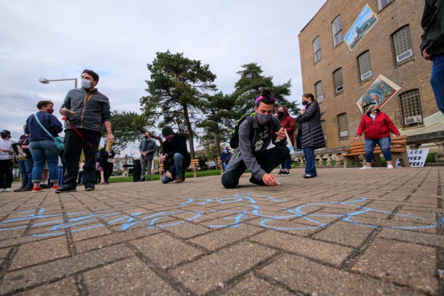 Vigil attendees write messages of support Friday on the ground of Memorial Park.
