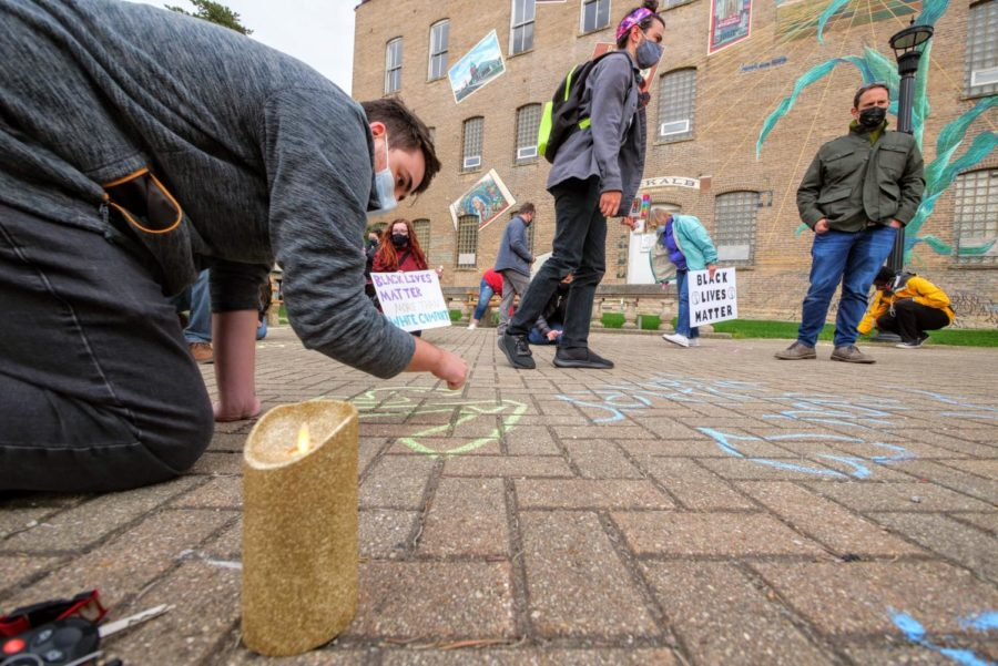 A battery-powered candle sits on the ground Friday as vigil participants write messages of support with chalk.