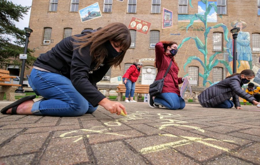 Vigil participants write messages of support for Black Lives Matter Friday on the ground of Memorial Park in DeKalb