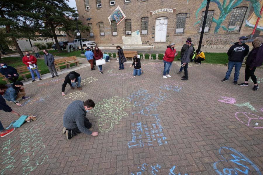 DeKalb activists use sidewalk chalk to write encouraging messages at Fridays vigil.