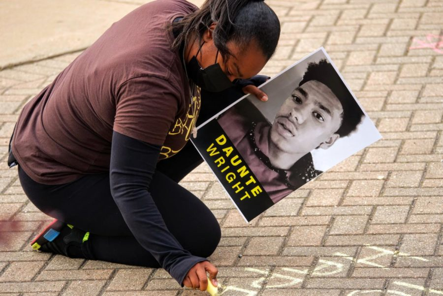 DeKalb community member Jessica Webb holds a poster of Daunte Wright while writing a message with chalk Friday.