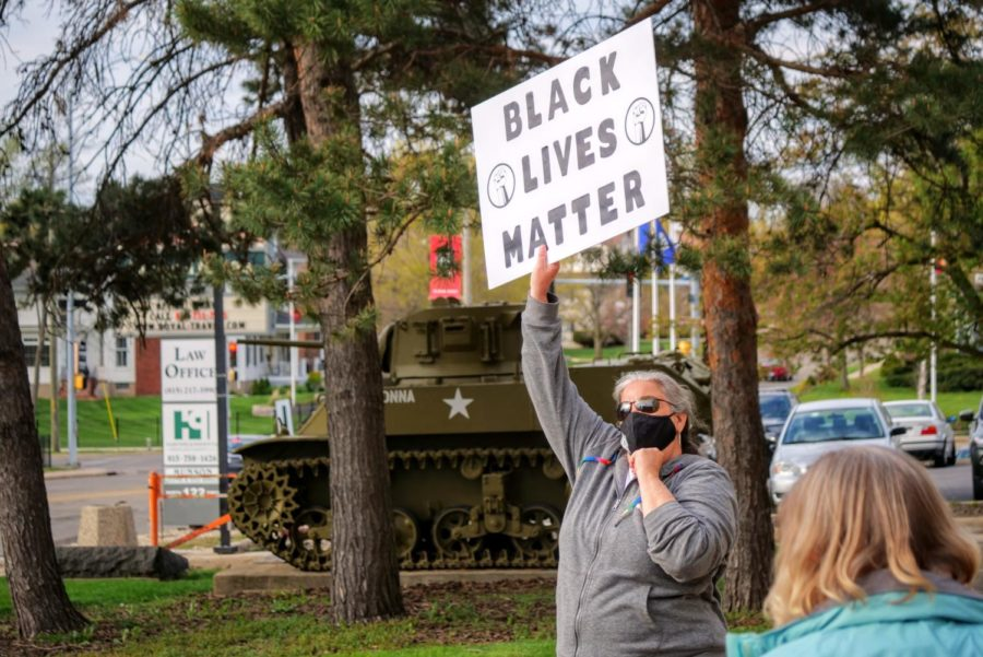 Vigil attendee holds a Black Lives Matter poster above her head Friday at Memorial Park.