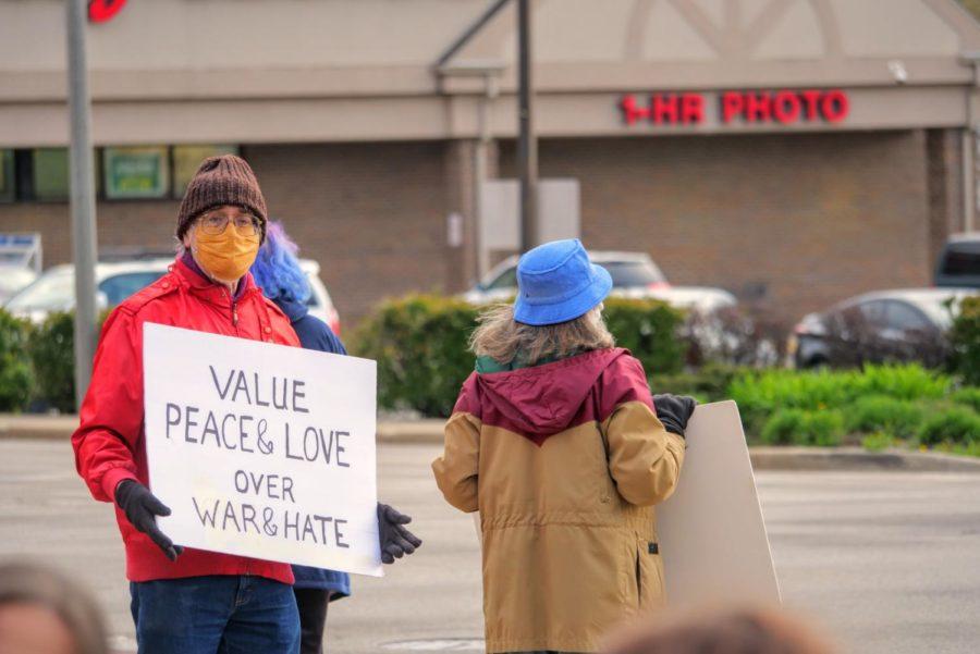 DeKalb community members hold up signs Friday to passing traffic at Memorial Park in DeKalb.
