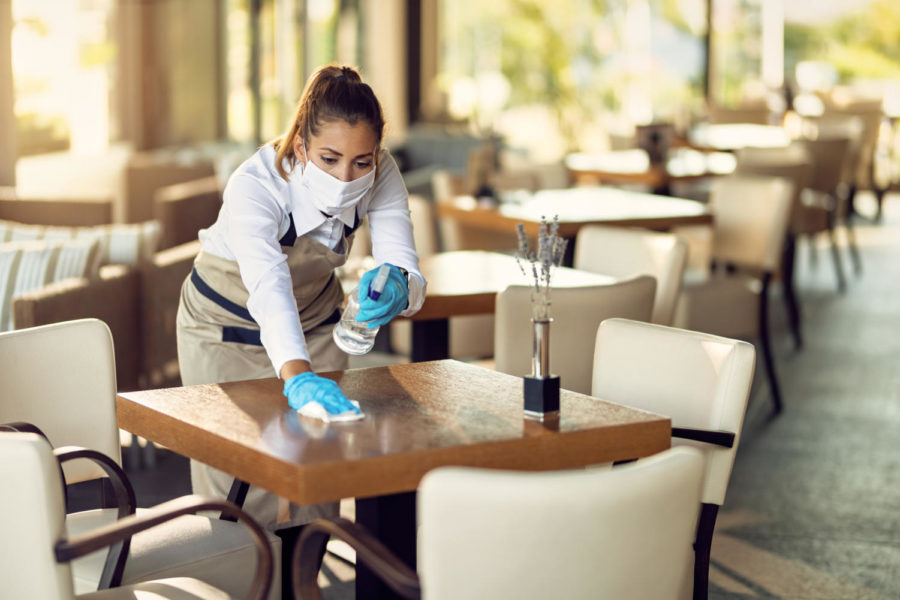 Waitress disinfecting tables while wearing protective face mask and gloves due to COVID-19 epidemic.