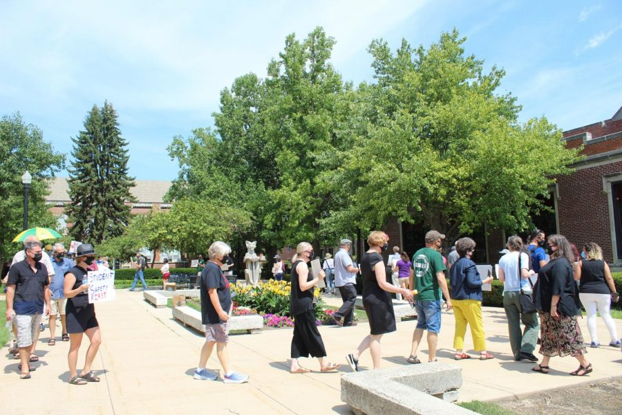 Faculty, instructors and staff hold signs and chant, Safety for Huskies, outside of Altgeld Hall.