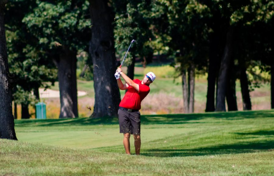 Senior Reece Nilsen hits an approach shot from the rough, Aug. 28 at Rich Harvest Farms during a fall qualifier. Nilsen returns with high hopes of contributing to the men's program.